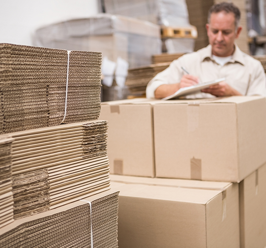 A man counting inventory with a range of custom and standard corrugated boxes